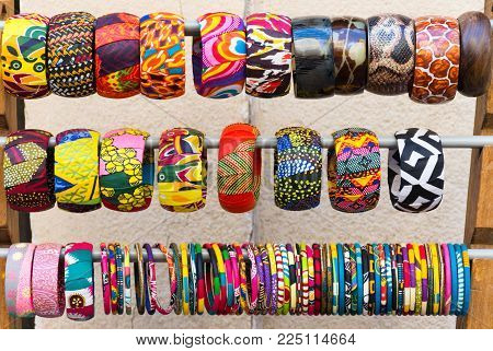 Close Up Of Multiple Colorful, Fabric Covered Bangle Bracelets On A Rack. Photographed In Natural Li