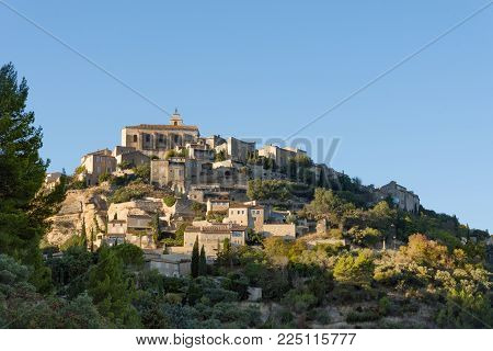 A Sunlit Hillside Village In Provence France With Deciduous Trees In The Foreground And Blue Sky Abo