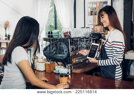 Asian woman barista wear jean apron suggestion coffee menu to customer at bar counter with smile emotion,Cafe restaurant service concept,Owner small business concept.