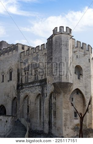 The Stone Battlement Of The Palais Des Papes In Avignon With Slit Windows, Turrets And Crenels.