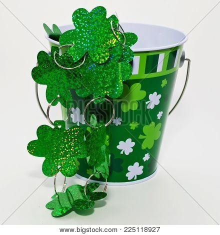 A string of large Shamrocks coming out of a small bucket adorned with Shamrocks for St Patrick's day