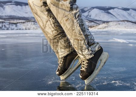 A skater man in black skates in winter warm ski pants shows a moon walk on the clear blue ice of the sacred Lake Baikal in winter on a mountain and sky background.