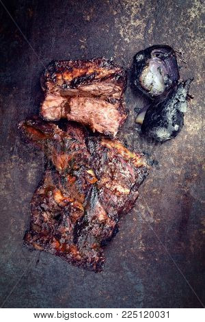 Barbecue caveman spare ribs St Louis cut with hot honey chili marinade and burnt onion as top view on an old rustic board