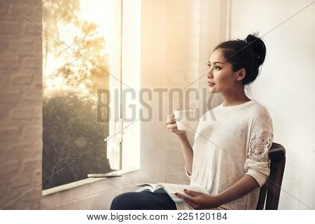 Thoughtful young beauty woman white cloth with book and cup of coffee sitting looking through the window, morning forrest landscape outside
