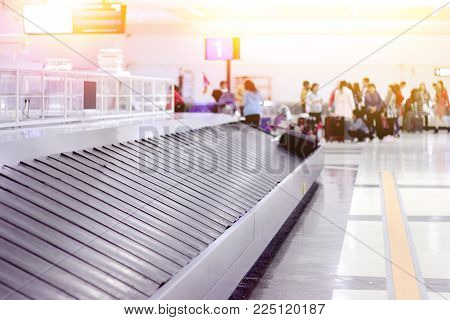 empty baggage conveyor belt at the airport with blurred waiting passenger background