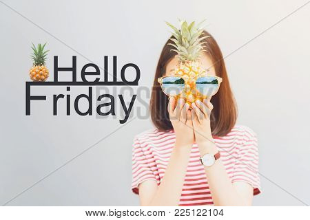 Young girl in red dress and hold pineapple in hand, Wear sunglasses with a reflection of the beach and island. And have a message Hello Friday. Concept summer travel.