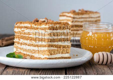 Honey cake Medovik on white plate. Russian cake. Layered biscuit cream cake