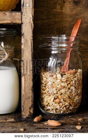 Homemade granola in jar and bottle of milk. Rustic kitchen pantry. Vertical, toned image