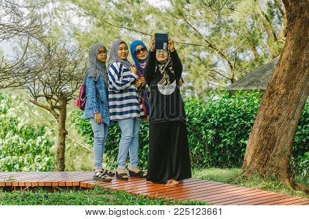 Kudat,sabah-feb 2,2018:happy Group Of Muslim Woman Taking Selfie With Smartphone Outdoors In The Tro