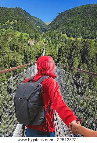 Couple summer vacation travel. Man walking on romantic honeymoon promenade holidays holding hand of wife following him at wooden bridge mountains landscape.Tourism vacation and travel.