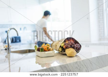 Colorful fresh vegetables and fruits with a bag of groceries shopping in the kitchen.Young handsome man cooking in background. Healthy eating concept