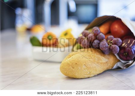 Close up bread and colorful fresh vegetables and fruits with a bag of groceries shopping in the kitchen.Healthy eating concept
