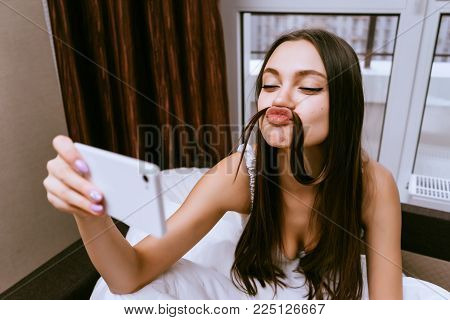 the woman is sitting on the bed and making a ridiculous selfie