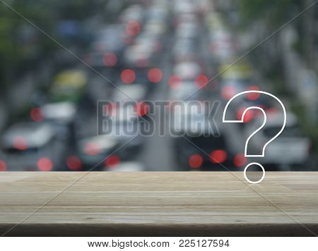 Question mark sign icon over blur of rush hour with cars and road, Customer support concept