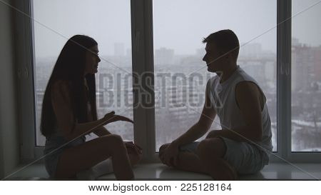 Family couple sitting on the windowsill, emotionally talking, arguing and gesticulating, silhouette shot