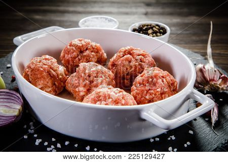 Raw meatballs on wooden background