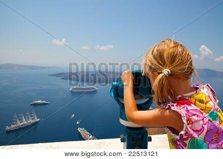 Girl Looking With Binoculars In Thira, Santorini, Greece