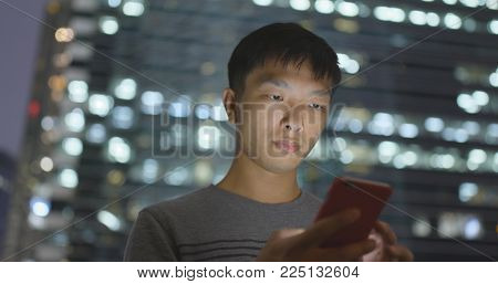 Man use of mobile phone in city at night
