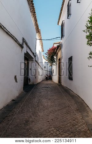 Cordoba, Spain - April 10, 2017: Old typical street in the jewry of Cordoba with white walls decorated with flowers