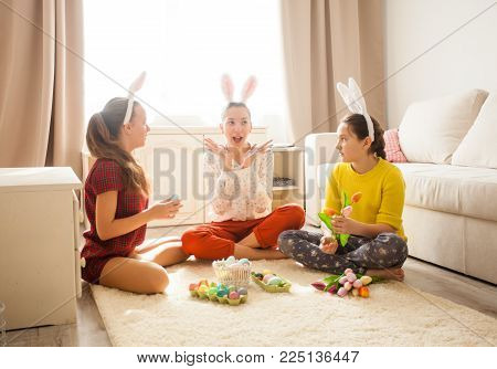 Girlfriends  in bunny ears sitting on the floor and playing with Easter rabbit. The concept of preparation for Holiday