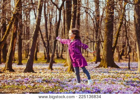Little girl enjoy the sun, she is dreaming and flying, inspired by blossom meadow of saffrons