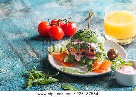 Homemade avocado vegan burger with onion, carrot, cucumber, tomato, rice, arugula and cranberry sauce