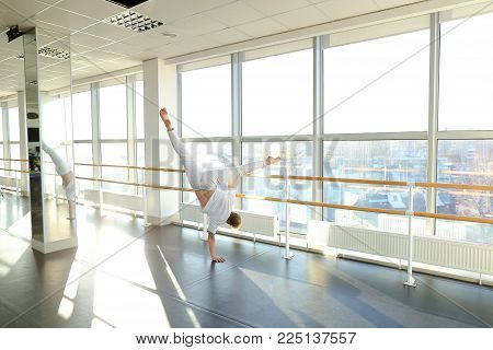 Athlete on first training after getting injured, guy feel pain but continue warm-up. Tattooed male wearing sport clothes standing near ballet barre in hall with big windows and mirrors. Concept of sportswear, well-equipped gym for group and individual wor