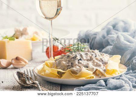 Fresh Tagliatelle pasta with mushrooms in a cream sauce on white plate