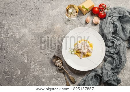 Fresh Tagliatelle pasta with Salmon in a cream sauce in white plate on gray background, top view with copy space