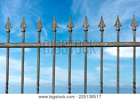 Close-up of a forged iron fence with arrows with blue sky and clouds