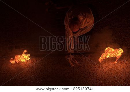 Fire Performance By A Street Artist At Night With Burning Torches