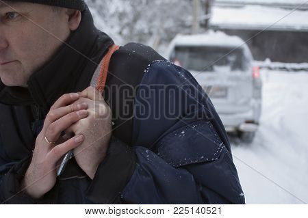Man towing a car trapped in snow with rope, outside cropped shot