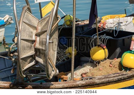 Close Up Of A Wooden Fishing Boat In The Harbor With A Winch For Nets And Buoys With Flags - Liguria