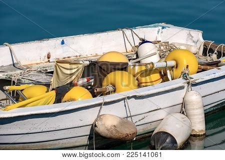Close Up Of A Small Fishing Boat With Fishing Equipment (buoys For The Nets) Docked In The Port - Li