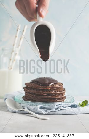 Chocolate pancakes with chocolate syrup, cook pours liquid chocolate from a sauce-boat. Blue background, breakfast concept, cooking.