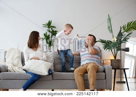 Picture of happy parents with son on gray sofa