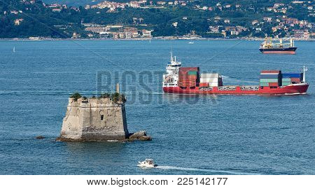 Container ship and the Scola Tower (Torre Scola) XVII century in the Gulf of La Spezia or Gulf of poets (Golfo dei poeti). La Spezia, Liguria, Italy