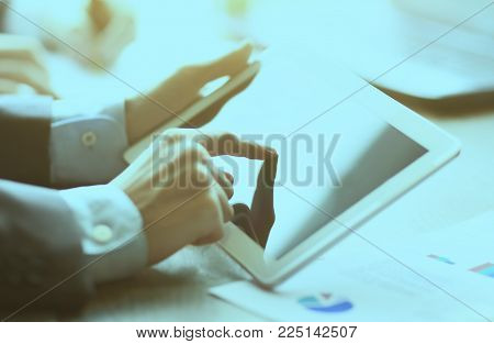 work of two young businessmen using touchpad at meeting