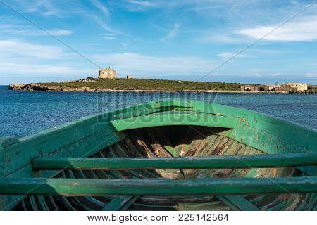 The Capo Passero Island (Cape Passero) with a boat of migrants. Portopalo, Syracuse, Italy, Europe