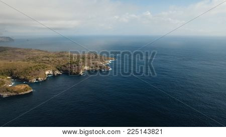 Aerial view of Rocky coast with high cliffs, sea surf with breaking waves on the coast, Nusa Penida, Bali, Indonesia. Ocean with waves and rocky cliff. Travel concept