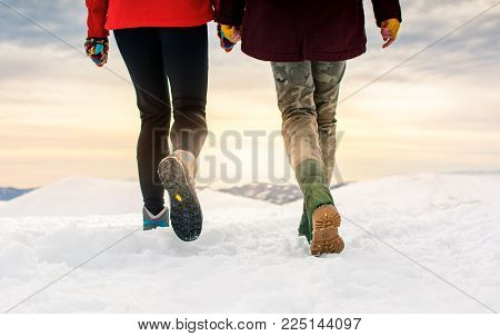 Friends hiking on the mountaintop covered with snow low angle view