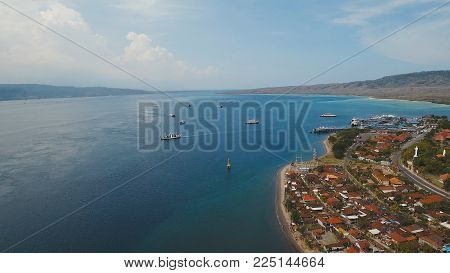 Aerial view ferry port Gilimanuk with ferry boats, vehicles and infrastructure, Bali, Indonesia. Ferries for transport vehicles and passengers in the port. Port for departure from Bali to the island of Java. Travel concept.