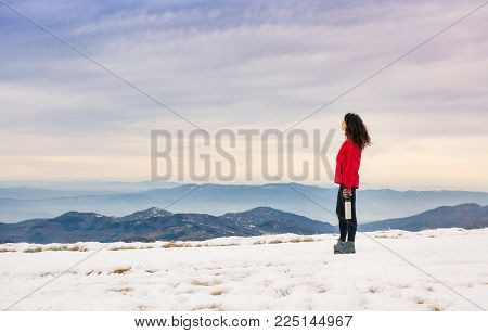 Female Hiker Admiring Winter Scenery On A Mountaintop Alone