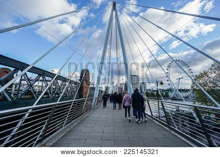 London / UK - November 13 2017: people walk on Queen's Golden Jubilee Footbridges