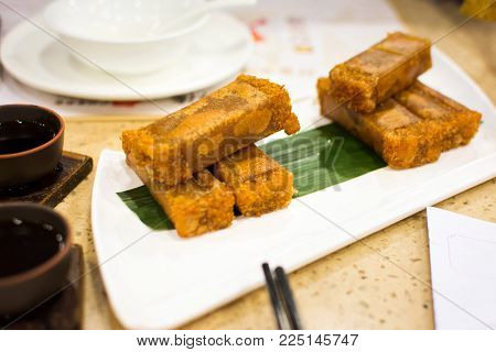 Fried coconut flavor sponge cake served on white plate on the table