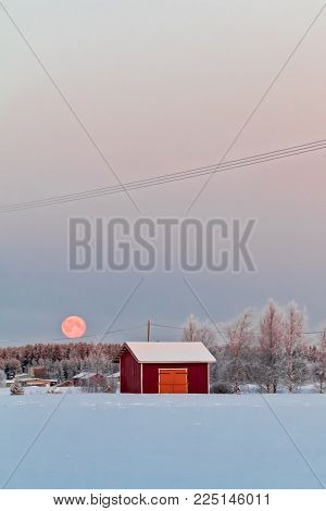 A Small Utility Hut In The Rural Finland Under The Setting Super Moon On A Cold Winter Day. The Wint