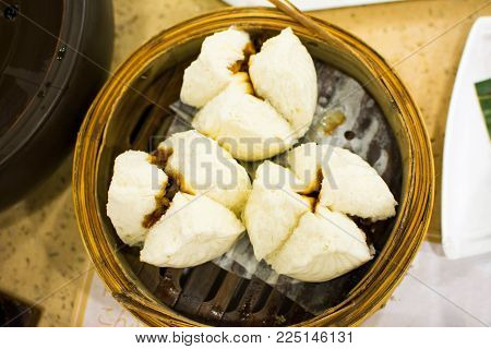 Steamed Bun with Barbecued Pork served on bamboo steamer in Chinese restaurant