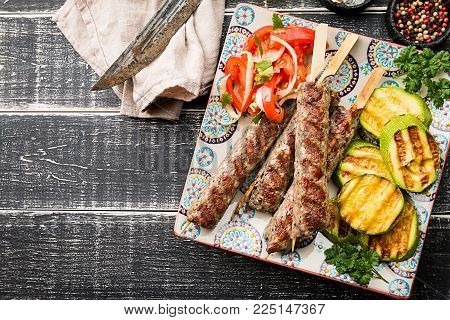 Traditional homemade grilled Turkish Adana Urfa Kebab, minced meat kebab, on a plate with tomato salad and zucchini over wooden background, top view