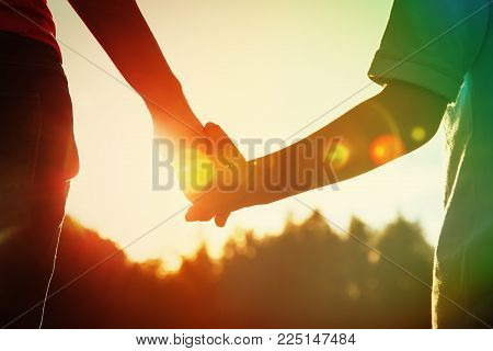 silhouette of parent and child holding hands at sunset, parenting concept