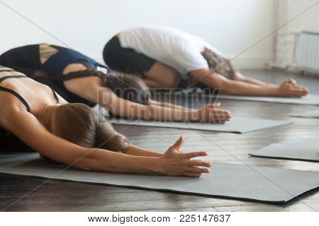Group of young sporty people practicing yoga lesson with instructor, stretching in Child exercise, Balasana pose, working out, indoor close up, students training in club, studio